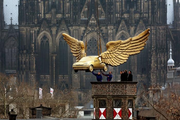 """Keulen.- Workers install a golden winged car on the roof of the City Museum in Cologne, western Germany, on April 4, 2013. The car, a creation by German artist HA Schult, is brought back to the roof after its restauration at Ford. AFP PHOTO / OLIVER BERG."""" (artdaily)"""