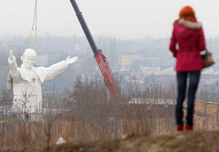 Polen - Een gigantisch standbeeld van paus Johannes Paulus II Pope John Paul II being readied for unveiling this weekend, in Czestochowa, Poland, Tuesday, April 9, 2013. The 13.8-meter (45.3-foot) white fiberglass figure will tower over the southern city of Czestochowa, home to Poland's most important Catholic pilgrimage site, Jasna Gora.  Funded by a private investor, the pontiff appears smiling and stretching his arms to the world.   (AP Photo/Czarek Sokolowski)